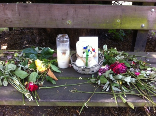 Flowers, a teddy and a candle left in memory